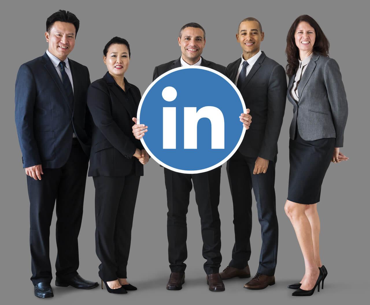 Cinco executivos, entre homens e mulheres, seguram o símbolo do Linkedin, demonstrando que o Linkedln funciona para encontrar trabalho