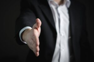Homem estende a mão para cumprimentar o recrutador após conseguir a recolocação profissional de executivo